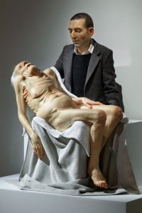 Middle aged man holding an older person who appears dead